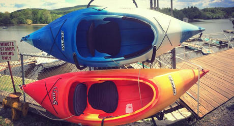 A blue kayak and an orange kayak at the marina of A Day Away Kayak Rentals