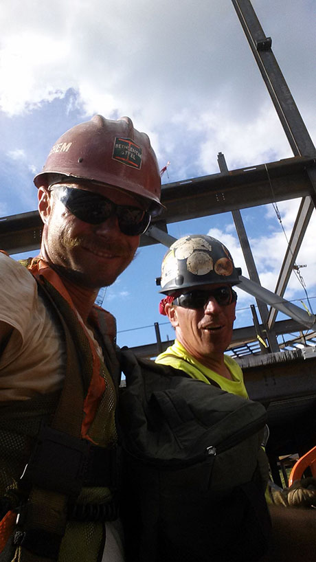 Ironworker Eric Brugeman and his coworker smile at the camera on a job site
