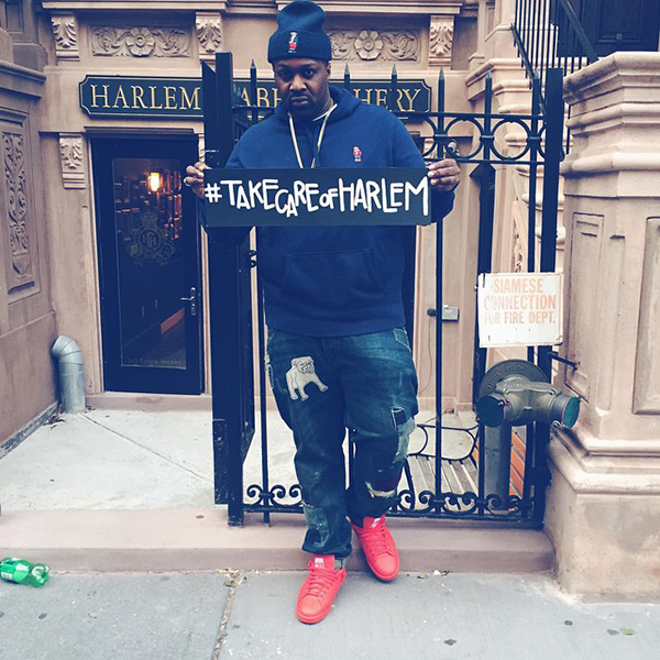 Lifestyle Rapper, Smoke DZA holds a sign that says #takecareofHarlem on the streets of NYC