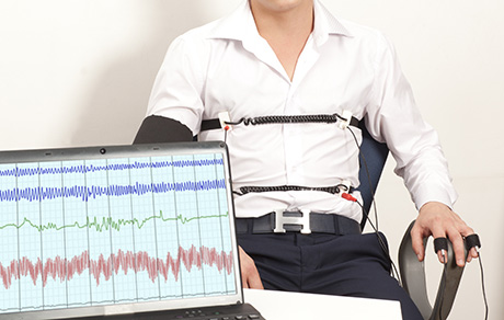 A man in the background and a polygraph lie detector in the foregroun